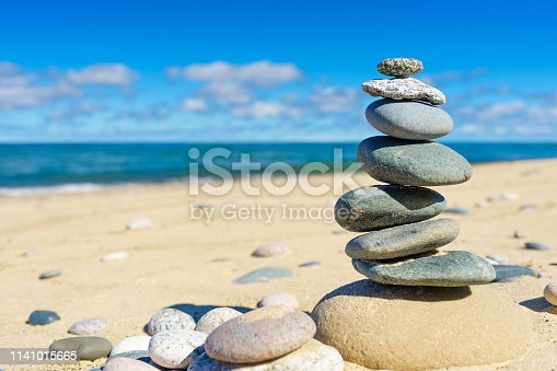 A rock cairn on a sandy beach.  Rock cairns are used as trail markers in places such as this secluded shore on Lake Superior.