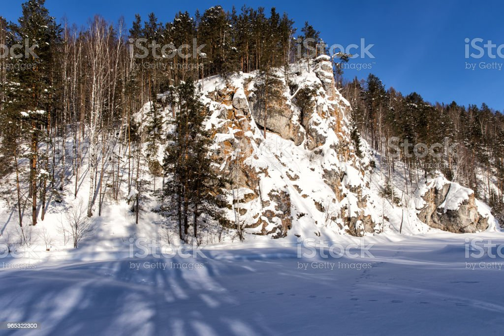 Rock cliff on the river bank. Winter landscape royalty-free stock photo