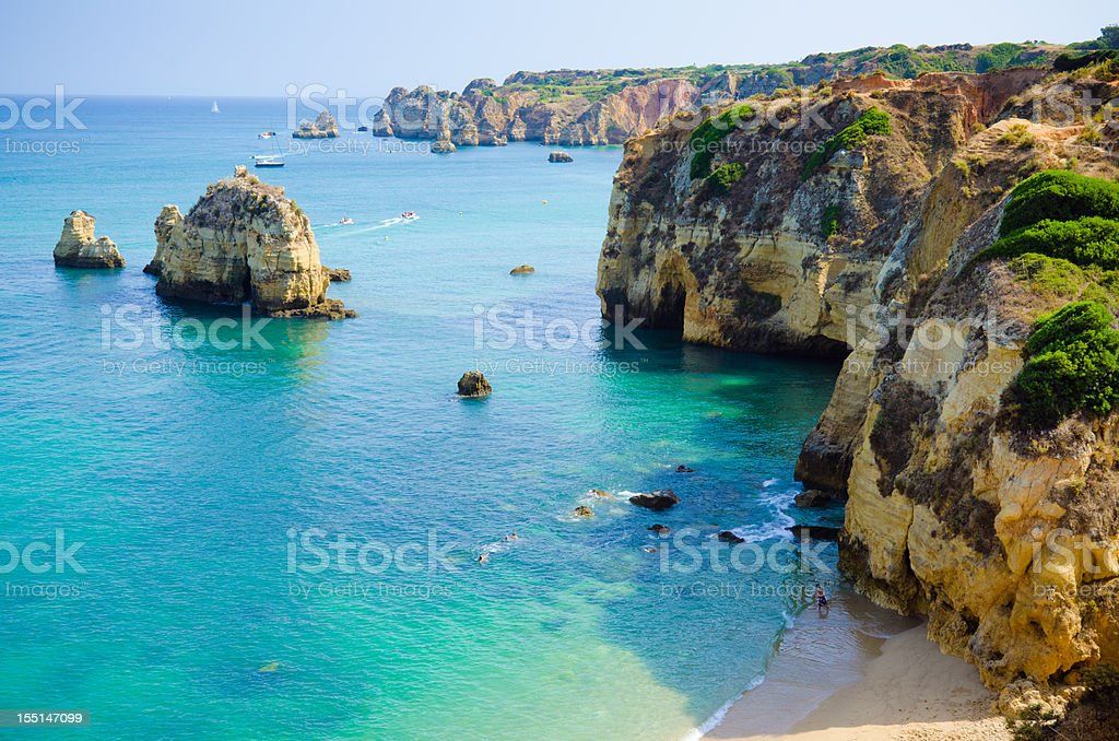 Rock cliffs bordering a teal sea in Lagos, Algarve, Portugal stock photo