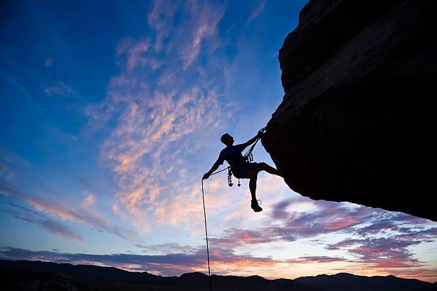 rock climber against an evening sky - rock climbing stock photos and pictures