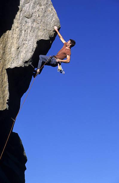 Rock Climber against blue sky stock photo