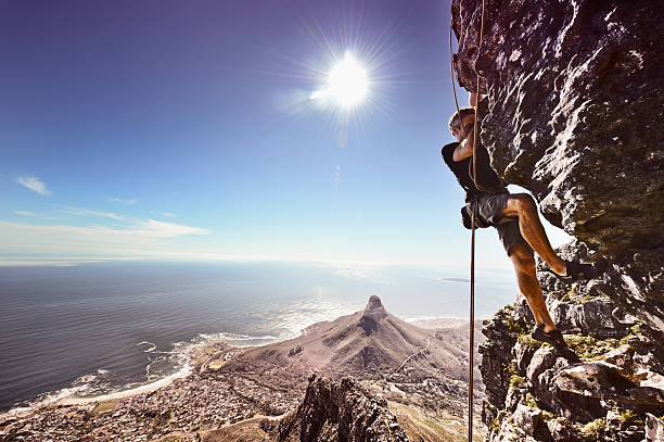 rock climber against steep cliff - table mountain south africa stock pictures, royalty-free photos & images