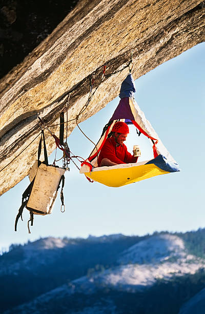 Rock climber bivouaced in a portaledge. stock photo