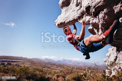Rock climber holding on to rock overhang as he boulders up mountain. He is strong and focussed.