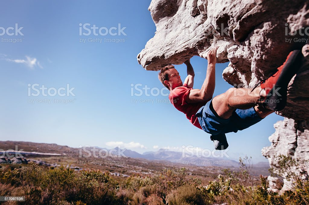 Rock climber bouldering outdoors on mountain in nature stock photo