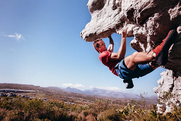rock climber bouldering outdoors on mountain in nature - rock climbing stock photos and pictures