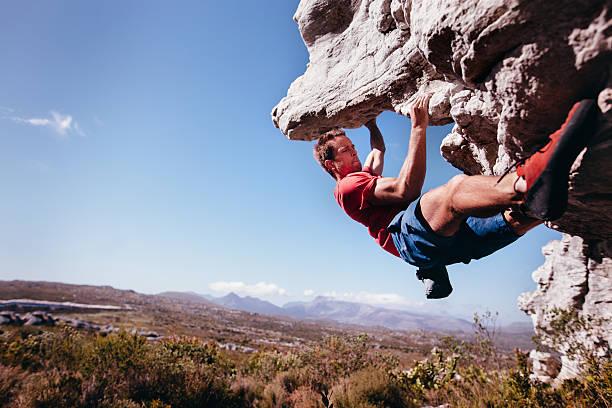 rocha alpinista bouldering ao ar livre nas montanhas de natureza - escalação em rocha - fotografias e filmes do acervo