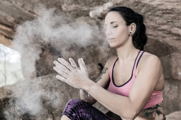 Rock climber clapping hands with magnesium chalk stock photo