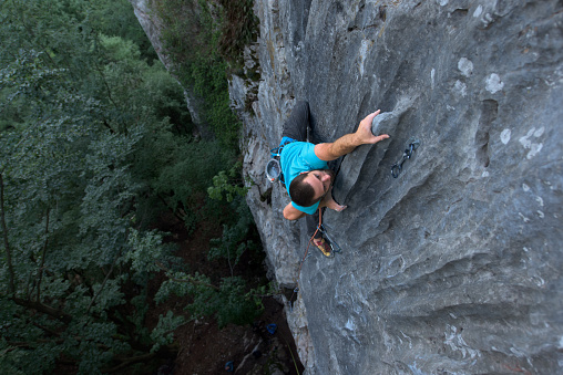 Rock climber climbing on a vertical rock wall outdoors in the nature