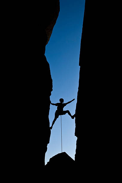 rock climber clinging to a cliff. - daredevil stock pictures, royalty-free photos & images
