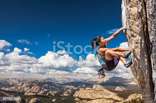 Female climber dangles from the edge of a challenging cliff.