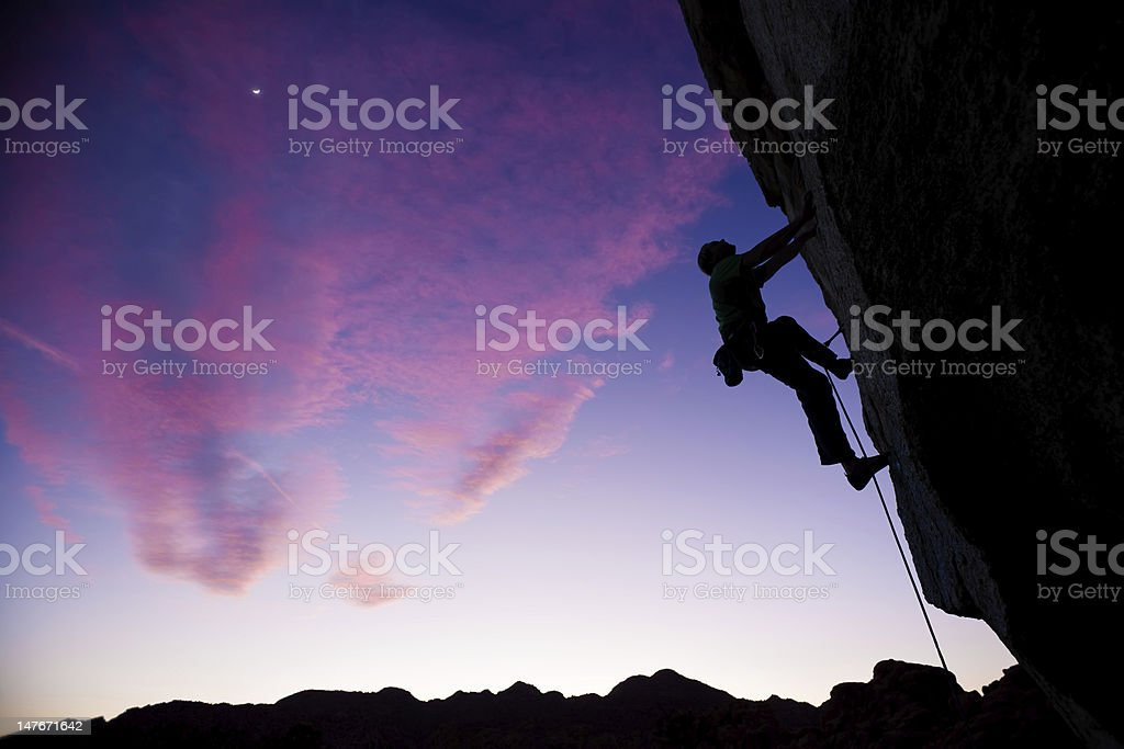 Rock climber clinging to an overhang. stock photo