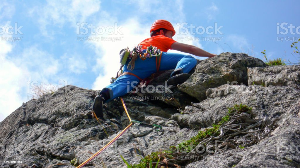 rock climber dressed in bright colors on a steep granite climbing route in the Alps stock photo