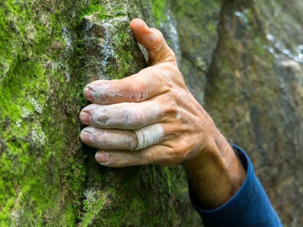 Rock climber hand closeup detail holding climbing stock photo