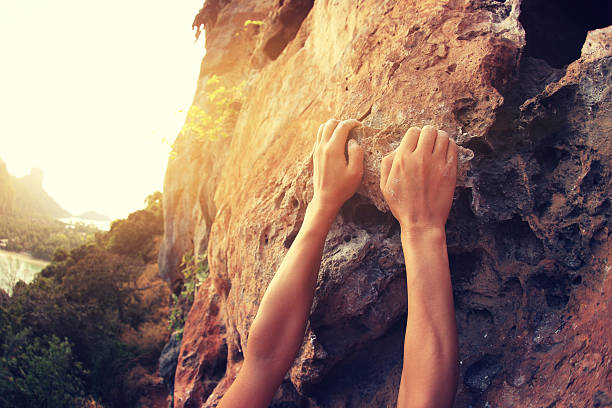 rock climber hands climbing at seaside mountain cliff rock - arrampicata su roccia foto e immagini stock