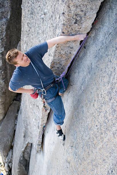 Rock Climber Leading up Crack stock photo