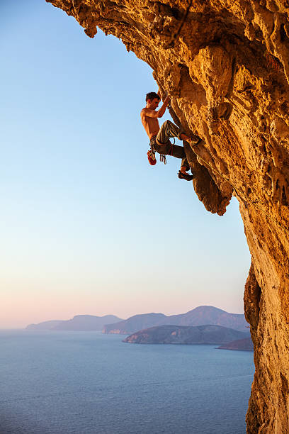 rock climber on overhanging cliff - rock climbing stock photos and pictures
