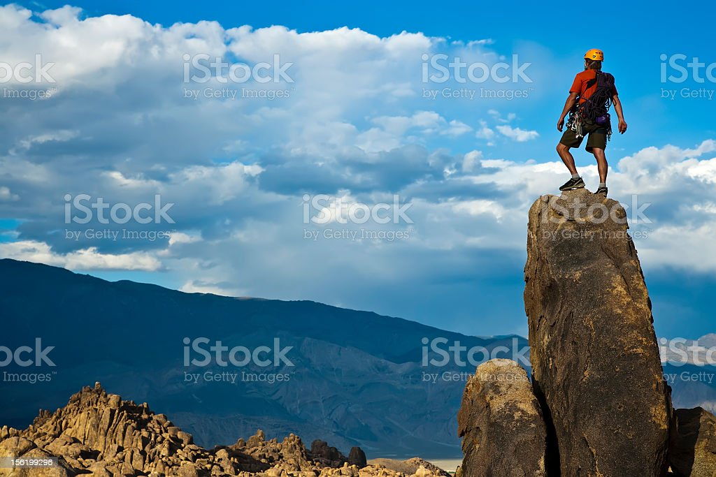 Rock climber on the top of the summit stock photo