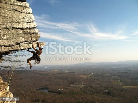 High adventure looms as a rock climber attempts an overhang in the Shawangunk Mountains, NY.