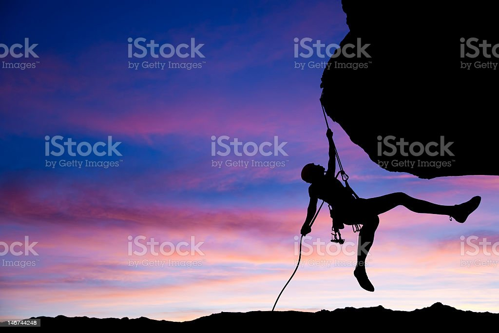 Rock climber rappelling at sunset royalty-free stock photo