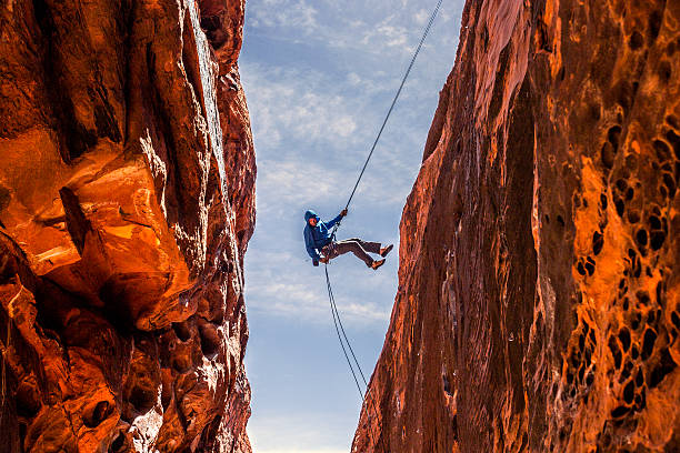 rock climber rappelling into a slot canyon - red rocks stock pictures, royalty-free photos & images