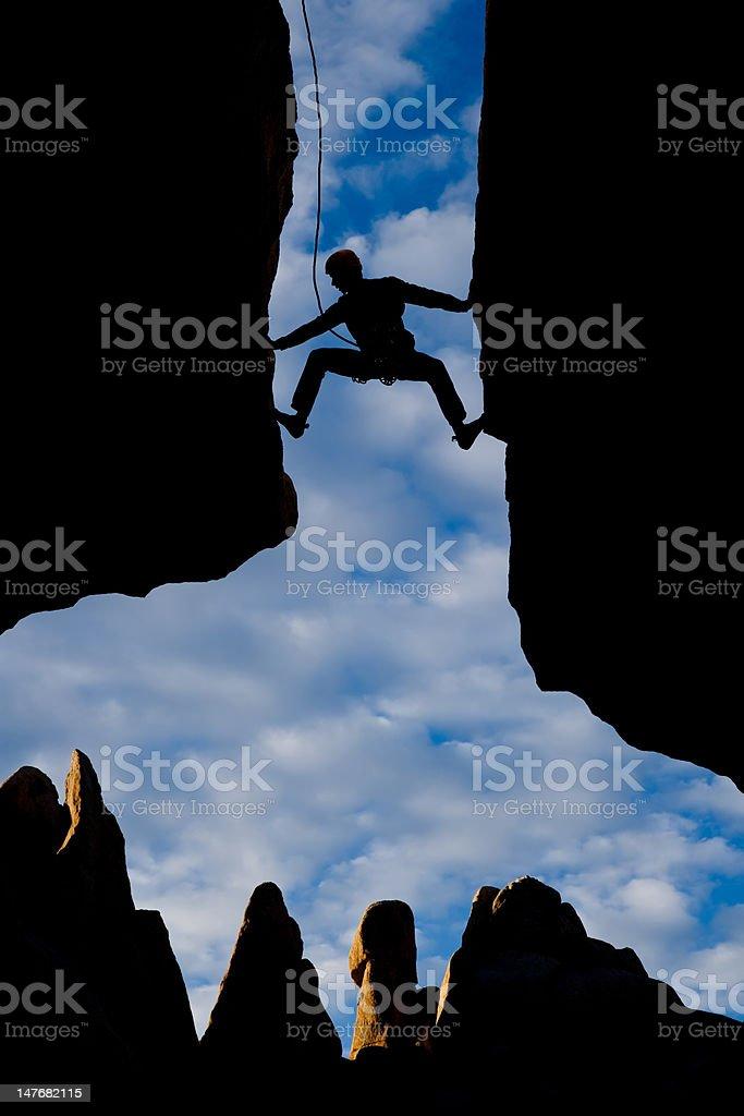 A rock climber reaching across a gap between two cliffs royalty-free stock photo