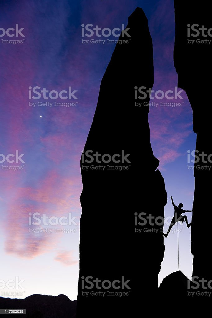 Rock climber reaching across a gap royalty-free stock photo