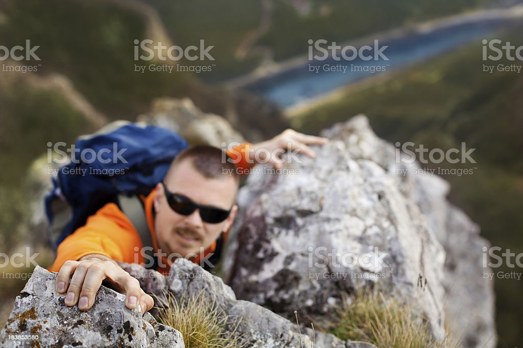 Rock climber reaching to the top of mountain royalty-free stock photo