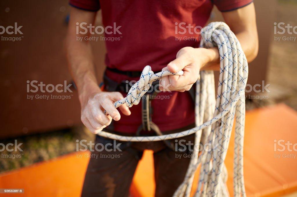 Seil Klettergurt Knoten : Ein kletterer einen knoten an einem seil eine person ist für den