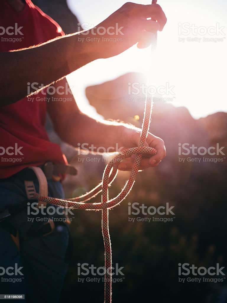 Rock climber tying knot with belaying rope before climbing stock photo