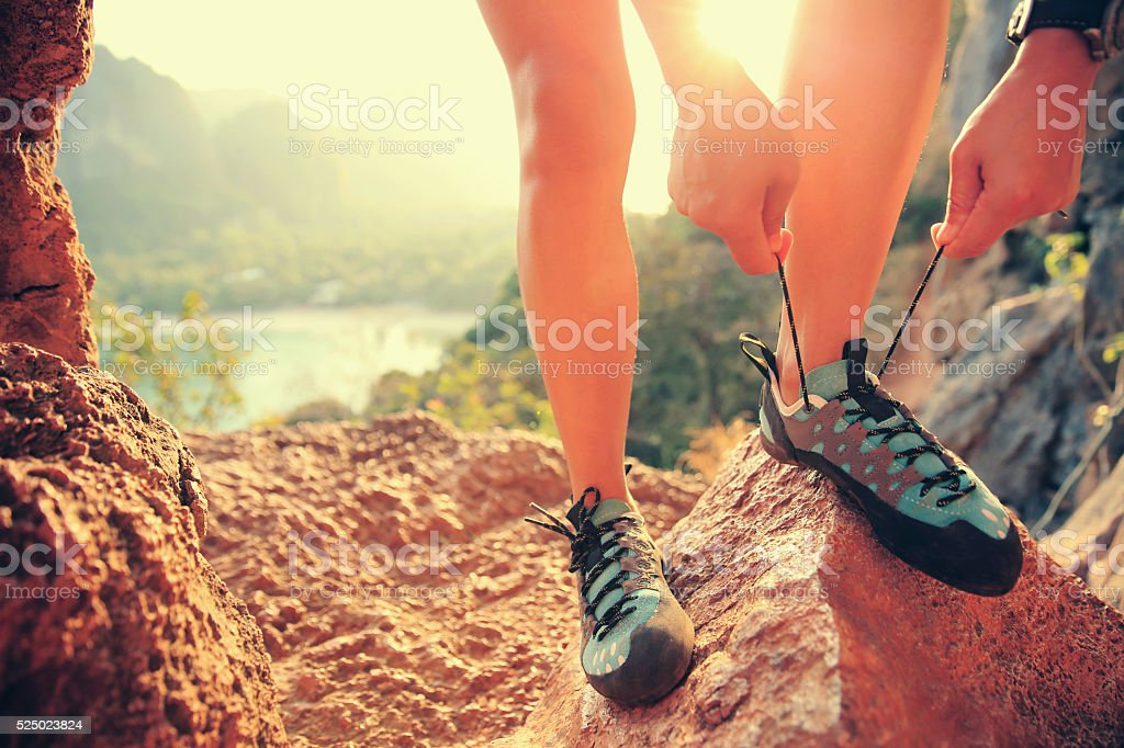 rock climber tying shoelace outdoor stock photo