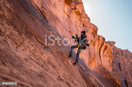 Outdoor photographer using climbing gear to scale a rock wall to get better photographs