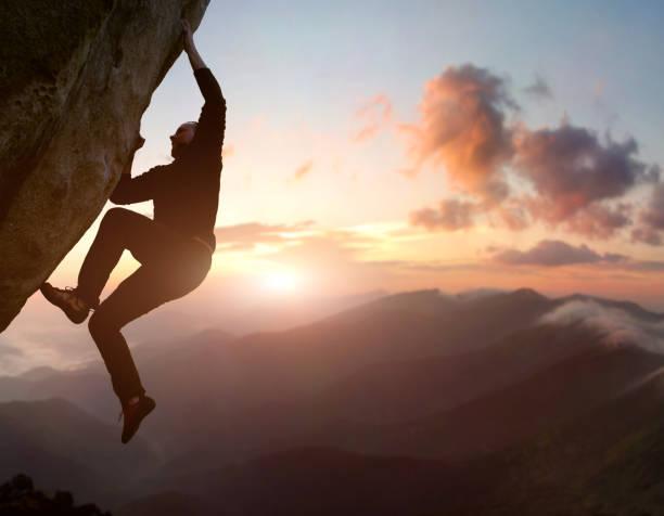 rotsklimmen. mannelijke klimmer proberen te verblijven op uitdagende rots, het overwinnen van obstakels. bergen en zonsopgang op de achtergrond - adrenaline stockfoto's en -beelden