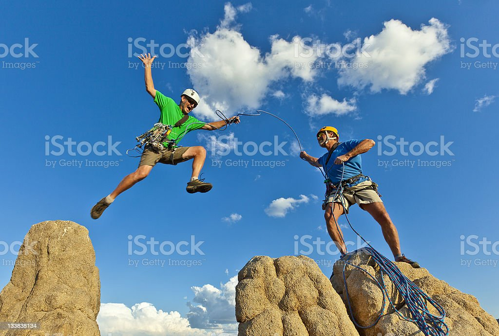 Team of climbers struggle to the summit of a rock pinnacle after a...