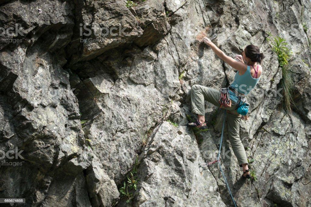 岩石攀爬的年輕的女子在義大利阿爾卑斯山: 爬山 免版稅 stock photo