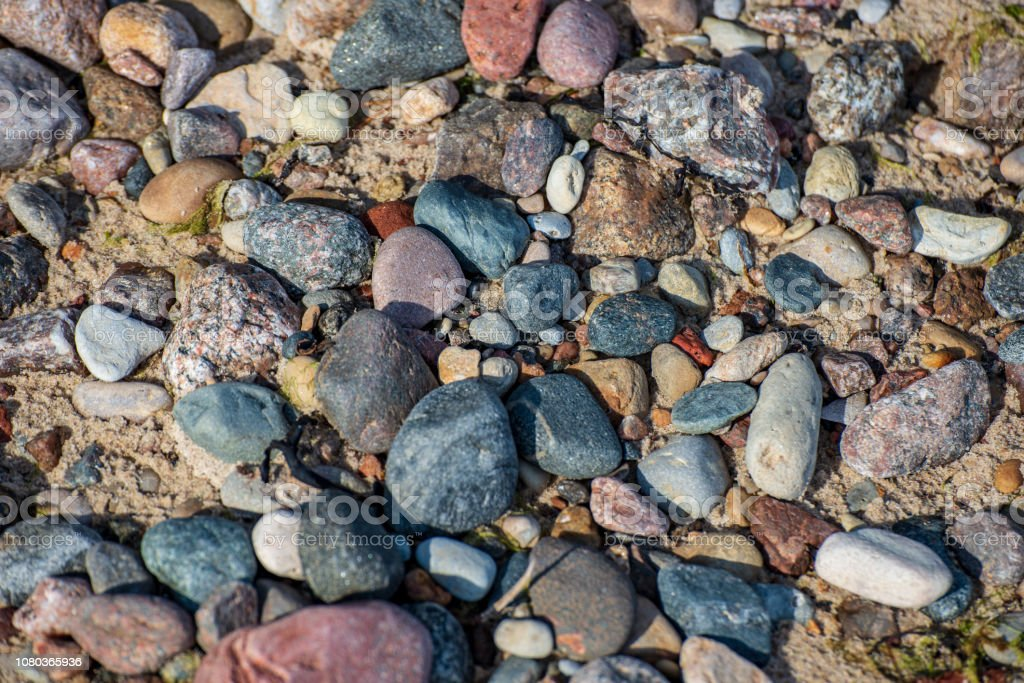 rock covered beach in countryside in Latvia, large rocks in water...