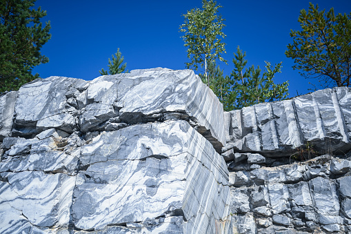 Rock cut raw surface of white and grey marble in the natural environment with trees and blue sky. Blue marble career texture. Background stone, industrial material for buildings and interior.