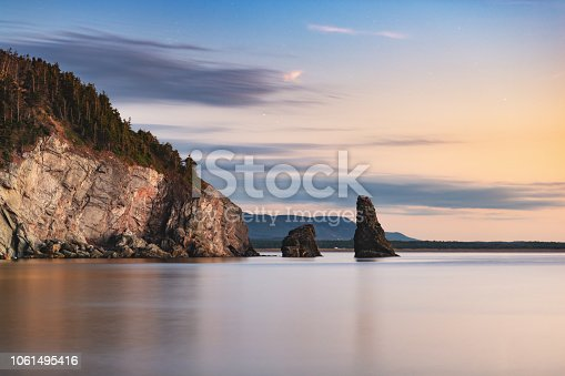 A long exposure of the calm ocean around a rock formation on Cape Breton Island, Nova Scotia.