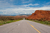 Red Rock formation on the side of the road on highway 84 in New Mexico near Ghost Ranch, Abiquiu with a blue cloudy textured sky