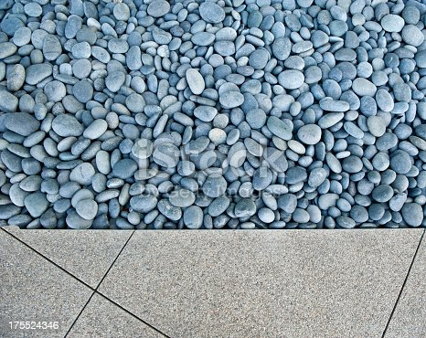 An arrangement of smooth river rocks encased in poured concrete in the public area of a corporate skyscraper.
