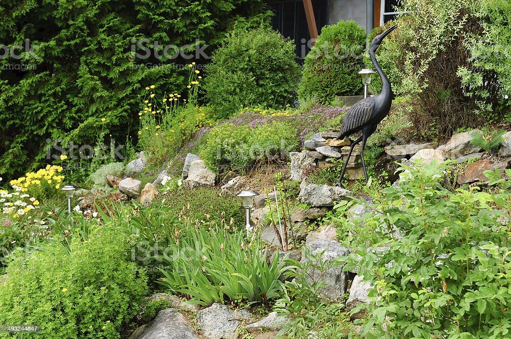 rock garden with heron steel decoration stock photo