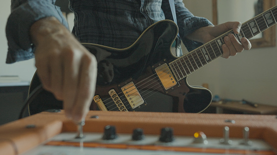 Rock guitarist playing guitar at home