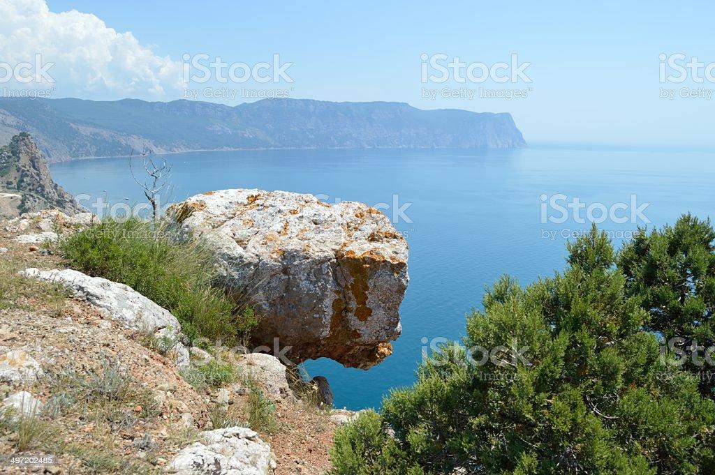Rock hanging over sea stock photo