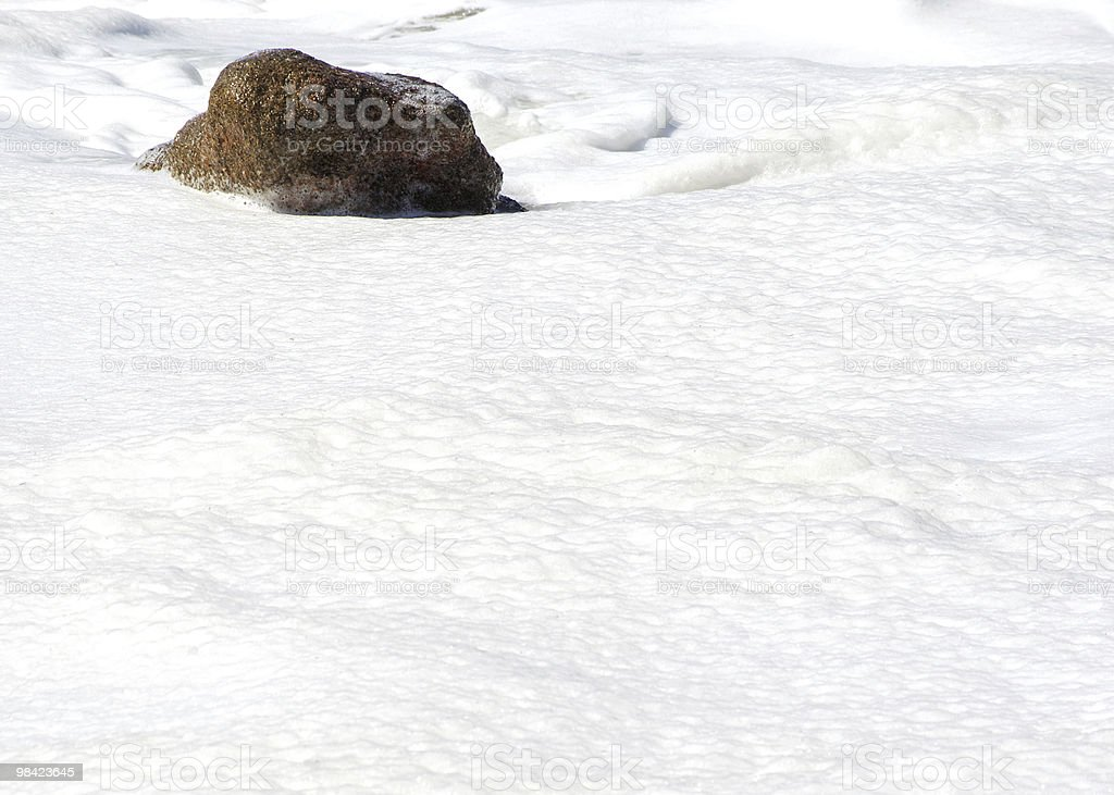 Rock in a sea of foam royalty-free stock photo