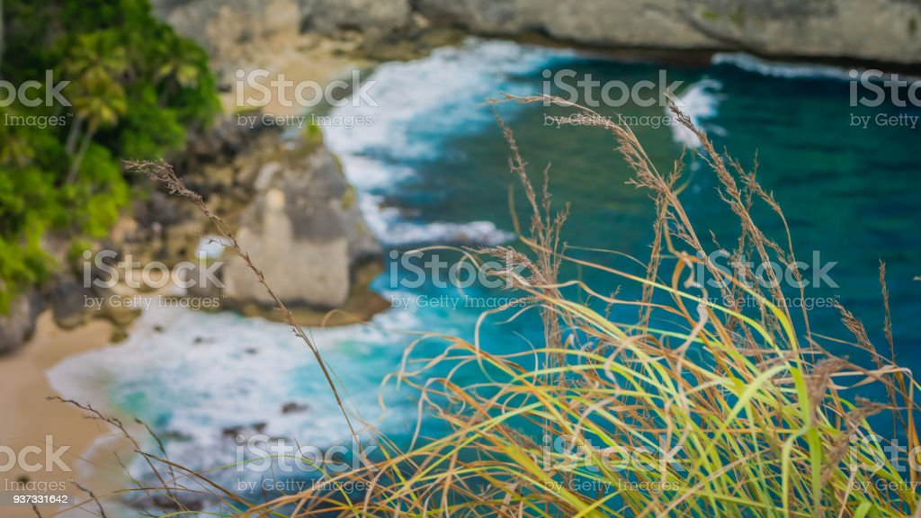 Rock in the ocean with beautiful palms behind at Atuh beach on Nusa Penida island, Indonesia stock photo