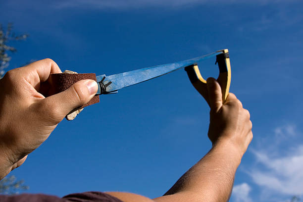 A rock is pulled back in an sling shot pointed to the sky stock photo