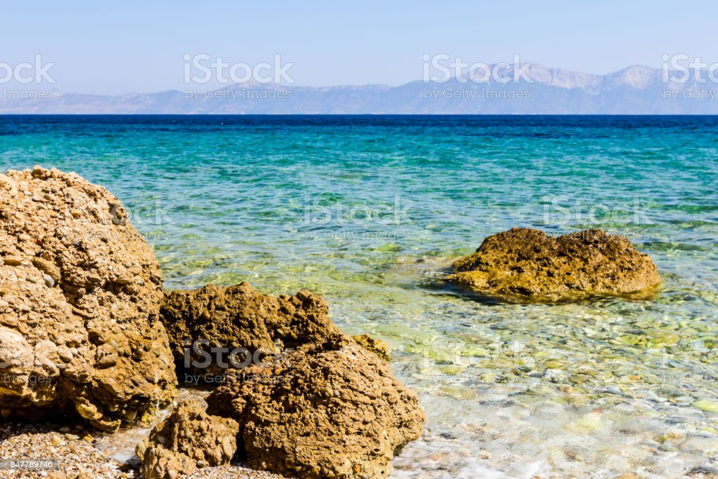 Rock is sticking out above the shoal water, above the sea level stock photo