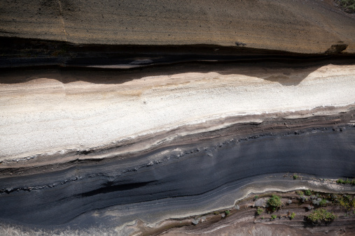 layers of rock, with some soil clinging to the rock.