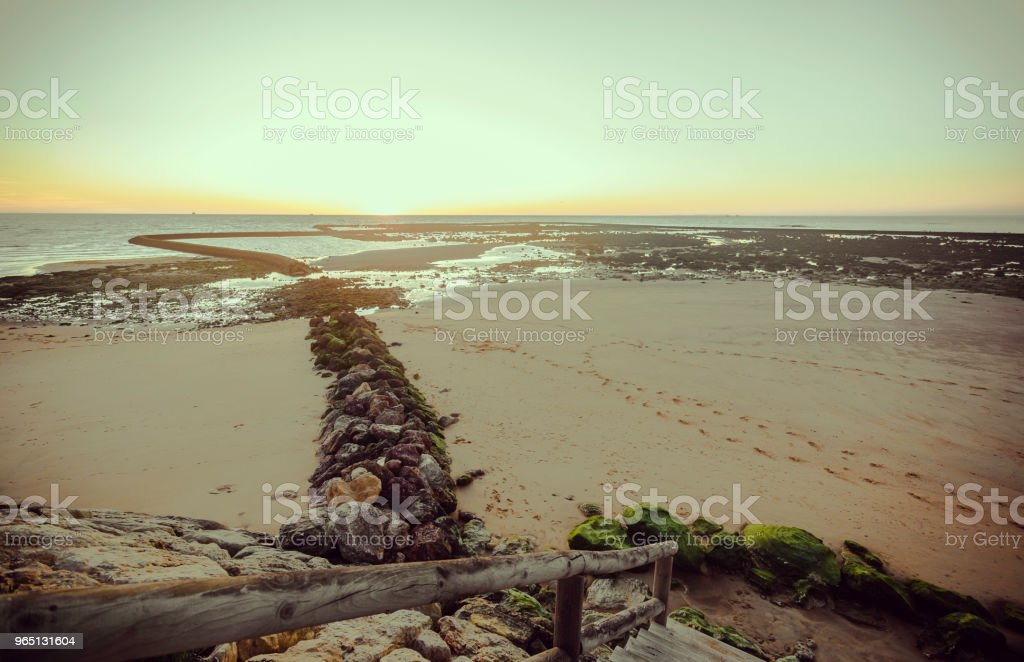 Rock lines to the sea at sunset with orange sky and railing in the foreground royalty-free stock photo