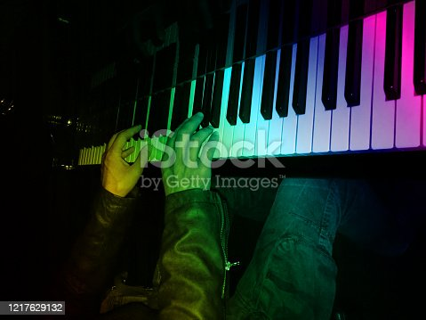 Close-up photo of musician's hands on piano keyboard in darkness with rainbow lighting